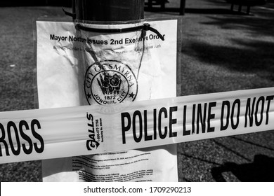 Smyrna,  GA / USA - Apr 13, 2020:  COVID-19 Police tape and city order shutting access to playground in black and white