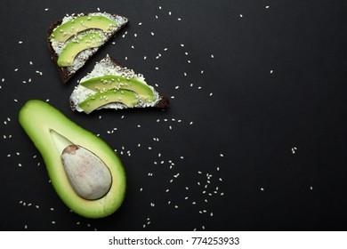 Snack avocado on dark rye bread with fresh sliced avocado and cream cheese top. Copy space.
