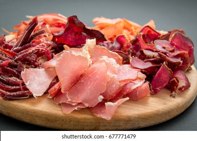 Snack to beer on a wooden board. Basturma, dried meat, dried squid, chips isolated on a black background.
