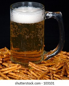 A snack of beer and pretzels on a black background