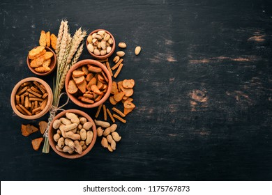 Snack for beer. Salted crackers, chips, nuts, peanuts, pistachios. On a wooden background. Free space for text. Top view.