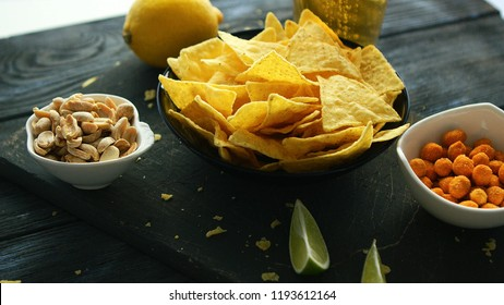 Snack board with served corn chips and nuts in bowls composed on wooden table for party