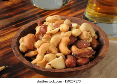 A snack bowl of mixed nuts on a bar counter with beer