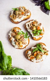 Snack bruschetta. Baked bread in the oven is spread with cottage cheese with garlic and spices, olives, walnuts and a sprig of parsley. On a light background basil green and red. Different angles