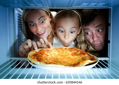 snack in fridge. All family looking at pizza in refrigerator.