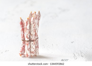 Snack fuet sausages on the wooden background