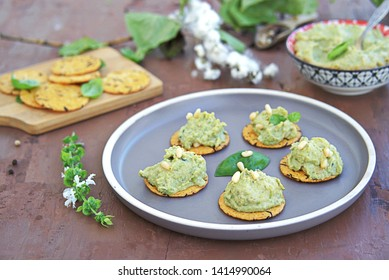 Snack, green pea spread with almonds and basil on unsweetened crackers on a brown clay plate. Healthy snacks.
