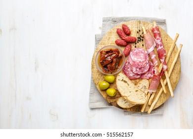 Snack ham, salami, bread sticks with ham on wooden background