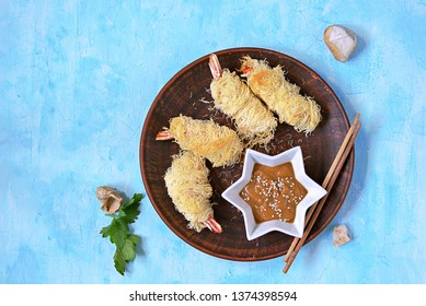 Snack or lunch, large shrimp in a crispy dough Kataify on a clay plate. Served with peanut sauce. Asian cuisine. Top view, copy space.