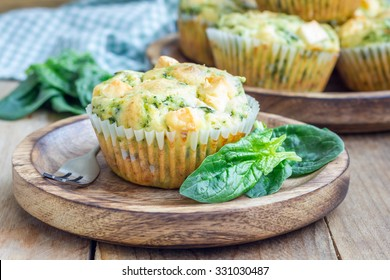 Snack muffins with spinach and feta cheese on a wooden plate