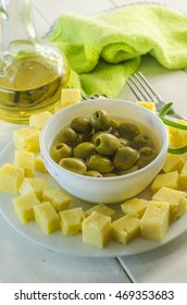 snack on a plate with olives and hard cheese