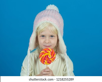Snack on when you please. Little child with sweet lollipop. Little girl hold lollipop on stick. Happy candy girl. Happy childhood food.