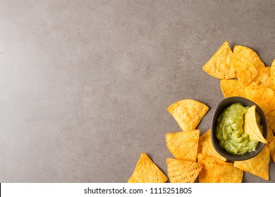 Snack for a party, chips with a tortilla, nachos with sauces: guacamole. Mexican food. Dark background. Top view. Copy space.