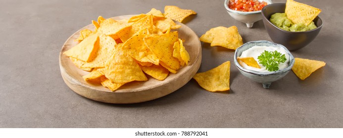 Snack for a party, chips with a tortilla, nachos with sauces: salsa with tomatoes, sour cream and guacamole. Mexican food. Dark background.  Copy space.