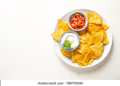 Snack for a party, chips with tortilla, nachos with sauces: salsa with tomatoes, sour cream. Mexican food. Bright white background. Top view. Copy spaceÑ?