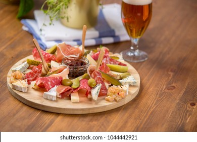 Snack platter with different cheeses, parma ham, salami sausage and pickles with cold beer on a wooden table background