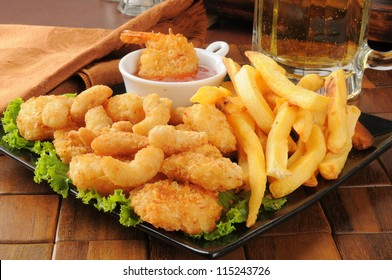 A snack platter with popcorn and coconut shrimp, fries and beer