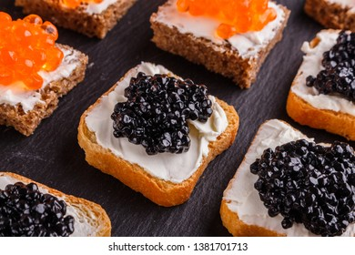 Snack with red and black caviar on a stone plate