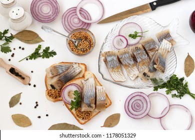 Snack from salted herring with red onion and mustard. White background, top view. Sliced herring on bread