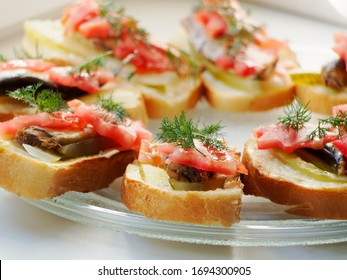 Snack sandwich with sprats cucumber and tomatoes and dill. Delicious sandwiches on a plate.