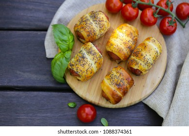 snack sausages in a dough on a wooden board