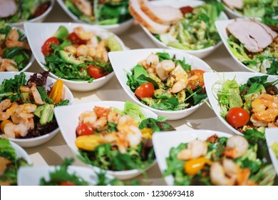 Snack of shrimp, avocado and greens on plates for guests of the event. Catering and snacks for guests and participants of events. Snacks, canapes and salads, cupcakes and vegetables on the table.