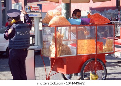 Snack street seller with orange trolley , January 2009, Mexico City, Mexico: A man sells traditional Mexican salty snacks from his colorful trolley while a policeman makes a call from a public phone.