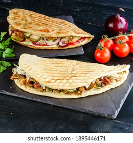 Snack. Takeaway food, street fast food. Pita bread sandwich with fresh vegetables and meat. Kebab in flat cake with vegetable