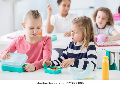 Snack time in a kindergarten class. Children opening their mint color lunch boxes with healthy vegetables. A bottle of orange juice on the desk.