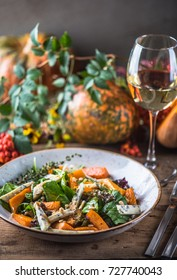 A snack of vegetables, cheese and a glass of wine on a wooden table. Autumn background - pumpkins, leaves, berries, plants. A healthy vegan fresh drink and food.