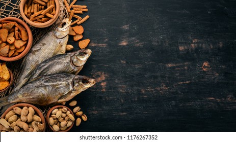 Snacks for beer. Salted crackers, Dried Fish, Chips, Nuts, Peanuts, Pistachios. On a wooden background. Free space for text. Top view.