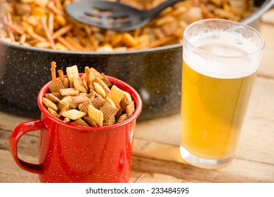 Snacks and Beer - This is a shot of a cold beer sitting next to a party mix. Shot on a wooden table.