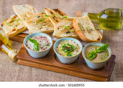 Snacks: Meat pie, fish Riet and hummus with pesto - a healthy and delicious meal. Plate with snacks and toast, oil bottle close-up on the table.
