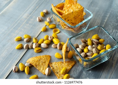 snacks in the Spanish tapas bar: crispy nachos and two kinds of pistachios (salty and yellow with saffron), snacks in square glass plates on a wooden table. selective focus and copy space