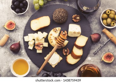 Snacks with wine - various types of cheeses, figs, nuts, honey, grapes on a gray background. Top view. Food background. Toned