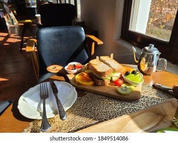 snadwich and fruit with fork and knife
