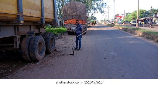 snake hanging on stick, holded by man on road at district Katni Madhya Pradesh in India shot captured on sep 2019
