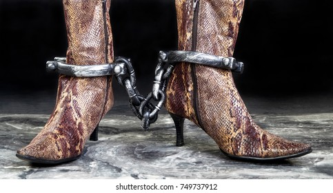 Snake skin boots in leg irons.