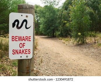 A snake warning sign by a dirt path along the banks of the Yarra River in Hawthorn, Melbourne, Australia