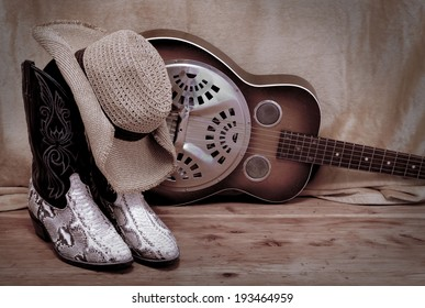 snakeskin cowboy boots with a cowboy hat propped on top in front of a dobro. Items are resting on rustic wooden surface in front of rough background. Image is desaturated and vignette added