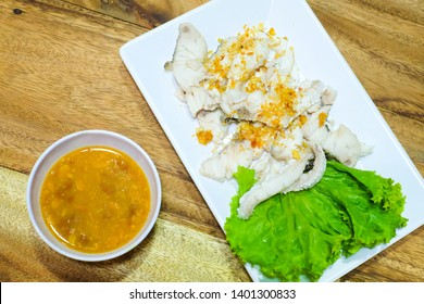 Snapper Scalded.Sliced white fish Place on a plate with sauce.With garlic sprinkled on fish meat.Thai food.at Khao Tom Shop(Street food shop).dinner