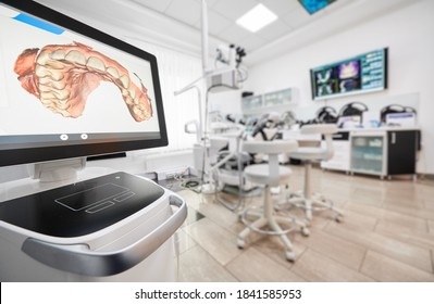 Snapshot of empty clean dental office. Interior of modern dental clinic. Computer screen with high precision digital jaw print on it on foreground.