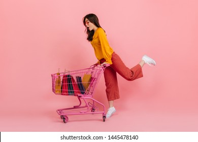 Snapshot full-length if girl shopaholic in bright outfit. Model carries supermarket trolley with packages