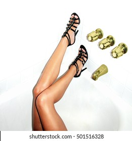 Snapshot style image of slender woman's legs in high heel shoes passed out drunk in a motel bathtub after a party