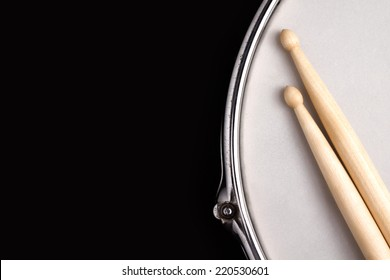 Snare drum with coated head and drumstick on black background with big copy space for text.