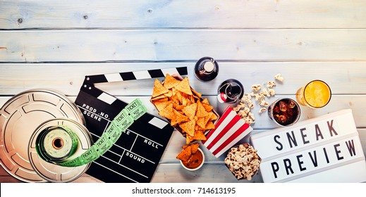 Sneak film preview panorama banner concept with cinema tickets, reels, nachos, popcorn, clapper boars, beer and fruit juice or cocktails on wood with copy space