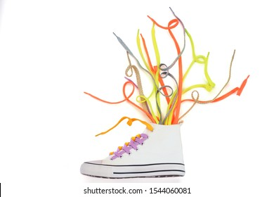 Sneaker and many colorful shoelaces on white background. Fashion trends and custom footwear design.