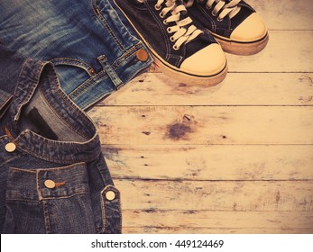 Sneaker shoe and fashionable jean denims on wooden background, vintage filter effect