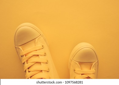 Sneaker shoes for youth lifestyle concept, pastel toned yellow footwear with copy space, top view