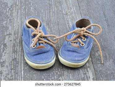 sneakers for baby on the old wood background